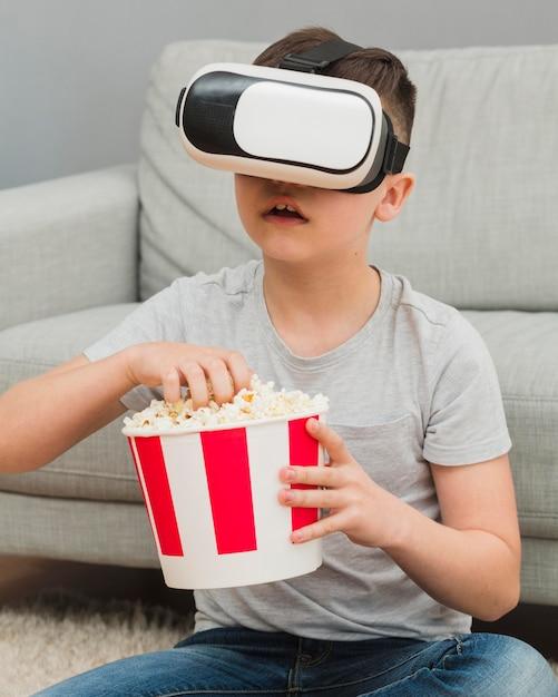 Vorderansicht des jungen, der film mit virtual-reality-headset und popcorn sieht Kostenlose Fotos