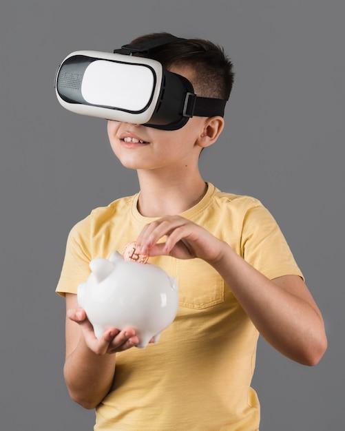 Vorderansicht des jungen, der geld beim tragen des virtual-reality-headsets spart Kostenlose Fotos