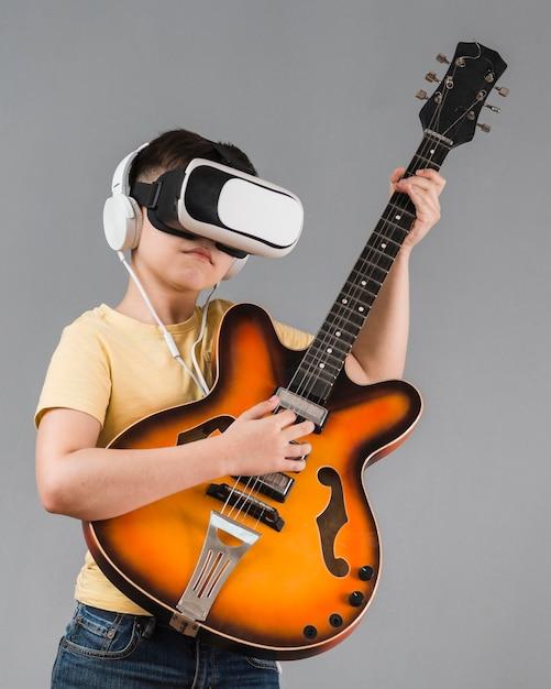 Vorderansicht des jungen, der gitarre spielt, während das virtual-reality-headset verwendet wird Kostenlose Fotos
