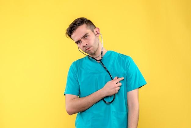 Vorderansicht des jungen männlichen arztes mit stethoskop auf gelber wand Kostenlose Fotos