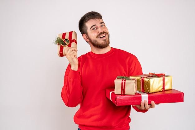Vorderansicht des jungen mannes im roten hemd, das weihnachtsgeschenke auf weißer wand hält Kostenlose Fotos