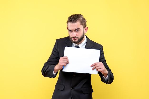 Vorderansicht des jungen mannes im schwarzen anzug, der weiße leere papierblätter mit platz für ihren text auf gelb ernsthaft hält Kostenlose Fotos
