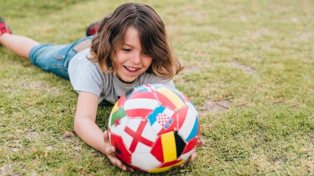 Vorderansicht des jungen spielend im gras Kostenlose Fotos