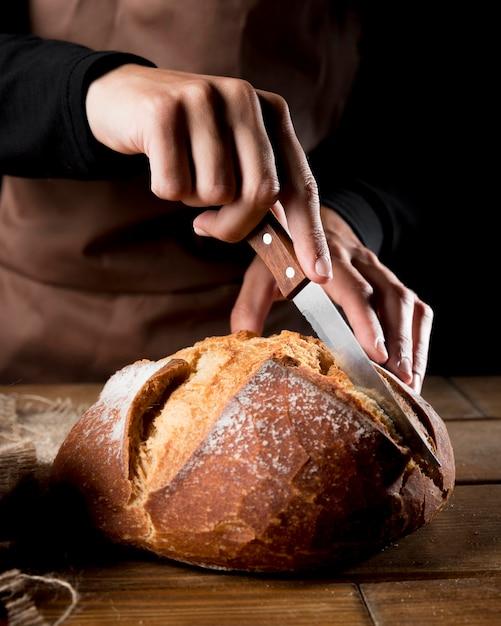 Vorderansicht des kochs, der köstliches brot schneidet Kostenlose Fotos