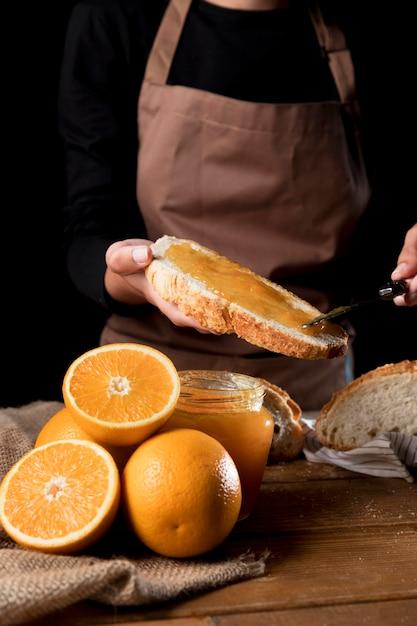 Vorderansicht des kochs, der orangenmarmelade auf brot verteilt Kostenlose Fotos