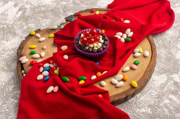 Vorderansicht des köstlichen schokoladen-brownies mit bunten bonbons auf der hellen oberfläche Kostenlose Fotos