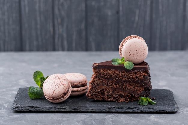 Vorderansicht des kuchens auf schiefer mit minze und macarons Premium Fotos