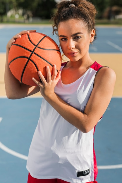Vorderansicht des mädchens, das basketballball hält Kostenlose Fotos