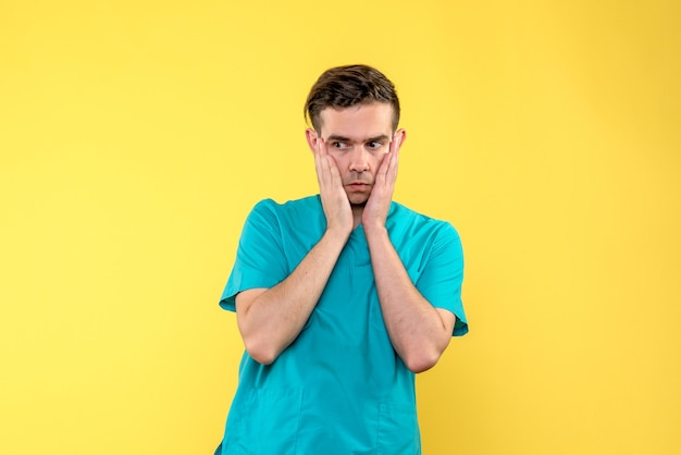 Vorderansicht des männlichen arztes besorgt auf gelber wand Kostenlose Fotos