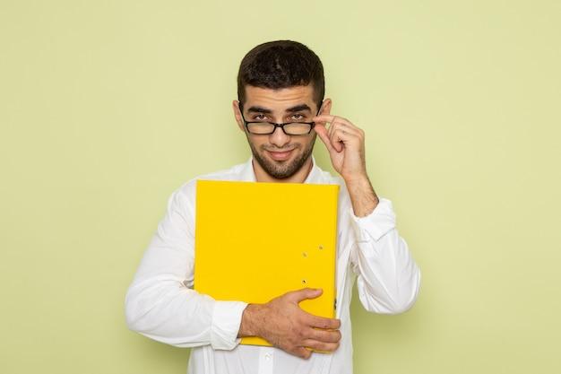 Vorderansicht des männlichen büroangestellten im weißen hemd, das gelbe datei auf der hellgrünen wand hält Kostenlose Fotos