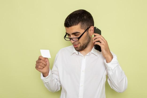Vorderansicht des männlichen büroangestellten im weißen hemd, das karte hält und am telefon auf grüner wand spricht Kostenlose Fotos