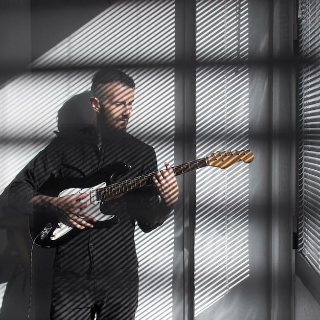 Vorderansicht des männlichen darstellers, der e-gitarre spielt Kostenlose Fotos