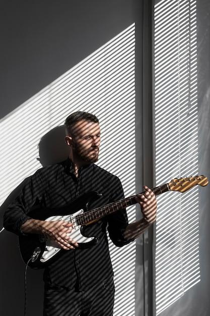 Vorderansicht des männlichen darstellers, der neben fenster beim spielen der e-gitarre aufwirft Kostenlose Fotos