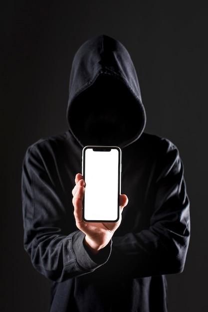 Vorderansicht des männlichen hackers, der smartphone hält Premium Fotos