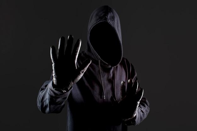 Vorderansicht des männlichen hackers mit handschuhen, die hand als stopp halten Premium Fotos