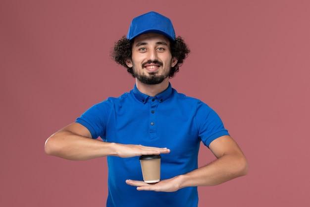 Vorderansicht des männlichen kuriers in blauer uniform und kappe mit lieferkaffeetasse auf seinen händen auf rosa wand Kostenlose Fotos