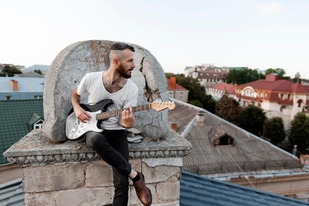 Vorderansicht des männlichen musikers auf dach, der e-gitarre spielt Kostenlose Fotos