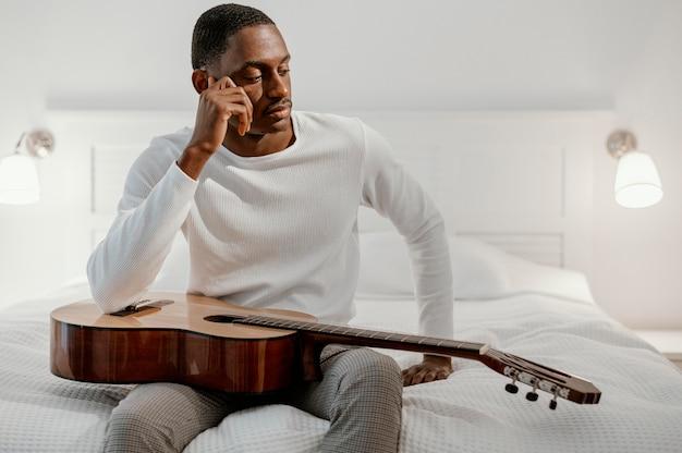 Vorderansicht des männlichen musikers auf dem bett mit gitarre Kostenlose Fotos