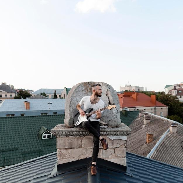 Vorderansicht des männlichen musikers, der e-gitarre auf dach spielt Kostenlose Fotos