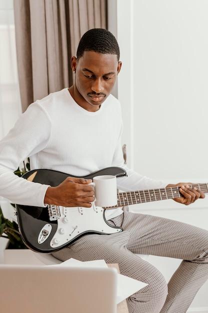 Vorderansicht des männlichen musikers, der e-gitarre und becher hält Premium Fotos