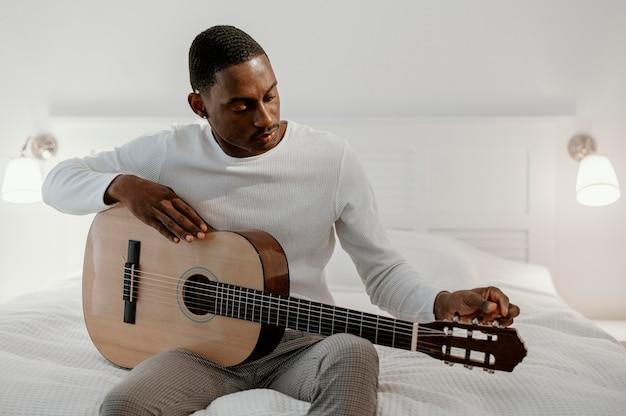 Vorderansicht des männlichen musikers, der gitarre auf bett spielt Kostenlose Fotos