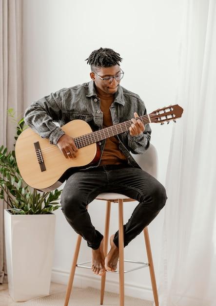 Vorderansicht des männlichen musikers, der zu hause gitarre spielt Kostenlose Fotos