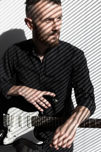 Vorderansicht des männlichen musikers mit e-gitarre neben fenster Kostenlose Fotos