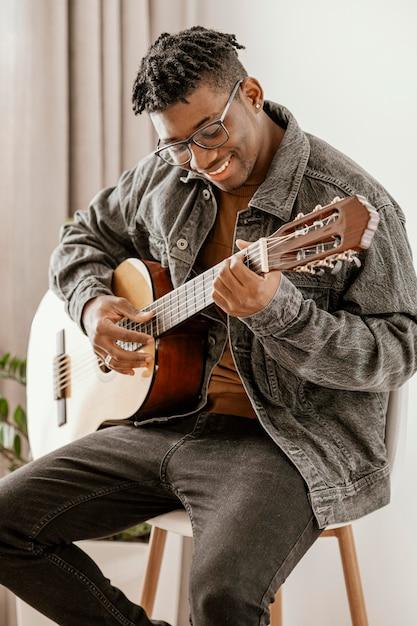 Vorderansicht des männlichen smiley-musikers, der zu hause gitarre spielt Kostenlose Fotos