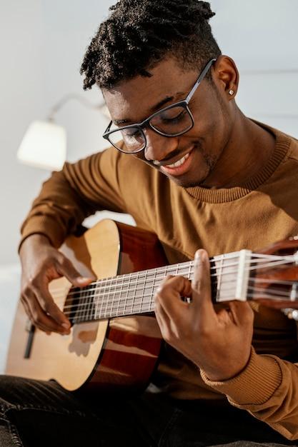 Vorderansicht des männlichen smiley-musikers zu hause, der gitarre auf bett spielt Kostenlose Fotos