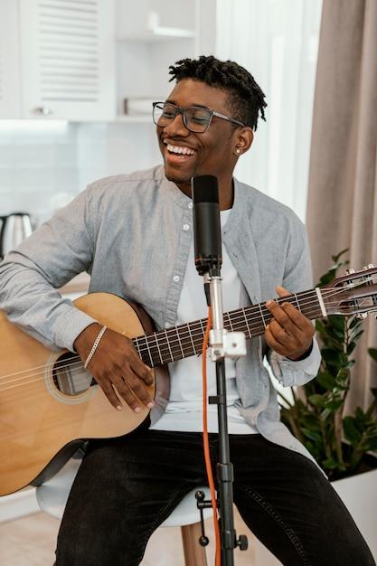 Vorderansicht des männlichen smiley-musikers zu hause, der gitarre spielt und singt Kostenlose Fotos