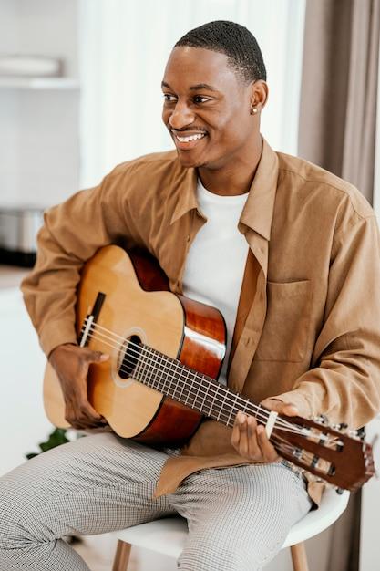 Vorderansicht des männlichen smiley-musikers zu hause, der gitarre spielt Kostenlose Fotos