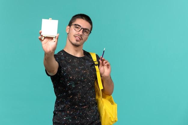 Vorderansicht des männlichen studenten im gelben rucksack des dunklen t-shirts, der quaste und staffelei an der hellblauen wand hält Kostenlose Fotos