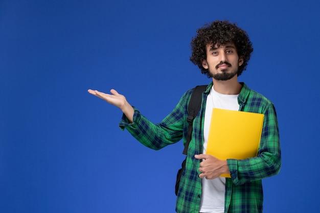 Vorderansicht des männlichen studenten im grünen karierten hemd, das schwarzen rucksack trägt und dateien an der blauen wand hält Kostenlose Fotos