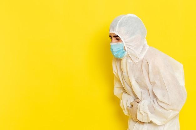 Vorderansicht des männlichen wissenschaftlichen arbeiters im speziellen weißen schutzanzug und mit maske, die seinen magen auf hellgelbem schreibtisch-wissenschaftsarbeiterchemie-farbgefahrfoto hält Kostenlose Fotos
