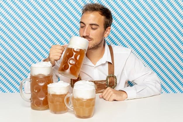 Vorderansicht des mannes blondes bier trinkend Kostenlose Fotos