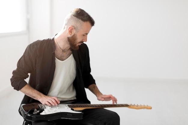 Vorderansicht des mannes, der e-gitarre spielt Kostenlose Fotos