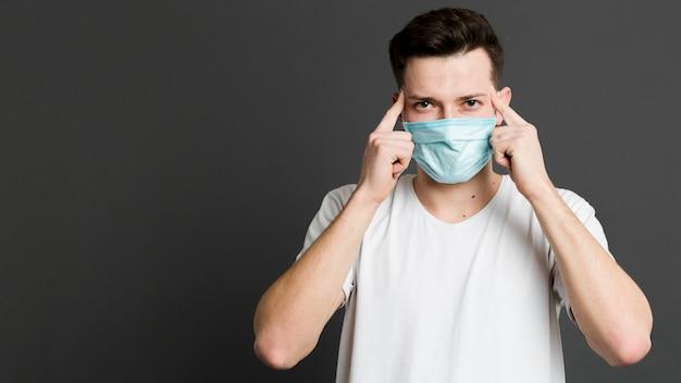 Vorderansicht des mannes, der eine medizinische maske trägt und auf seine schläfen zeigt Kostenlose Fotos