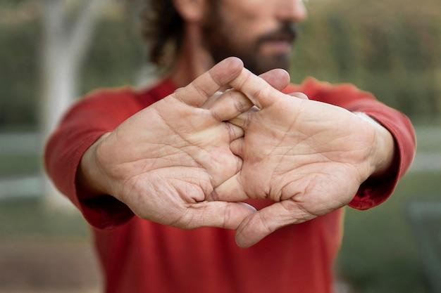 Vorderansicht des mannes, der seine arme draußen während des yoga streckt Premium Fotos