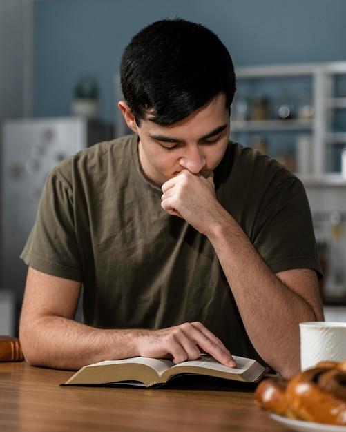 Vorderansicht des mannes, der von der bibel liest Kostenlose Fotos