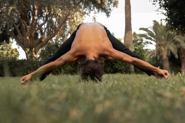 Vorderansicht des mannes, der yoga auf dem gras tut Premium Fotos