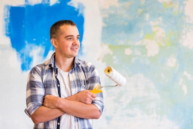 Vorderansicht des mannes eine farbenrolle halten Kostenlose Fotos
