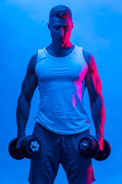 Vorderansicht des mannes im tank top, der gewichte hält Kostenlose Fotos