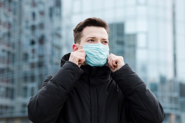 Vorderansicht des mannes in der stadt, die medizinische maske trägt Kostenlose Fotos