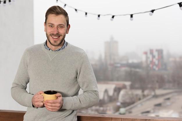 Vorderansicht des mannes in der strickjacke, die zu hause schale hält Kostenlose Fotos