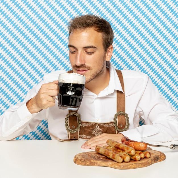 Vorderansicht des mannes mit bier und würsten Kostenlose Fotos