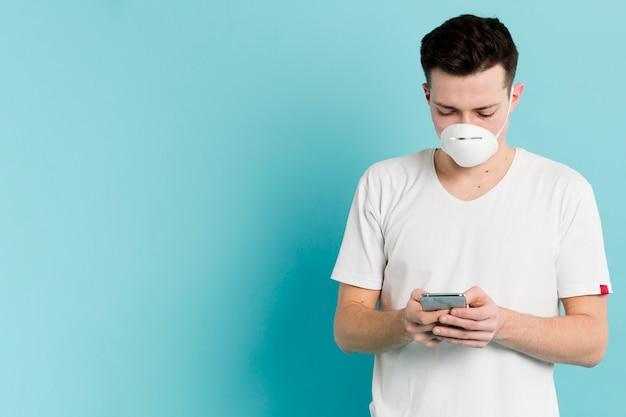 Vorderansicht des mannes mit der medizinischen maske, die coronavirus auf smartphone nachschaut Kostenlose Fotos