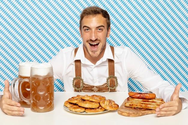 Vorderansicht des mannes mit deutschem lebensmittel und bier Kostenlose Fotos