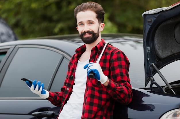 Vorderansicht des mannes mit reifen und schlüssel Kostenlose Fotos