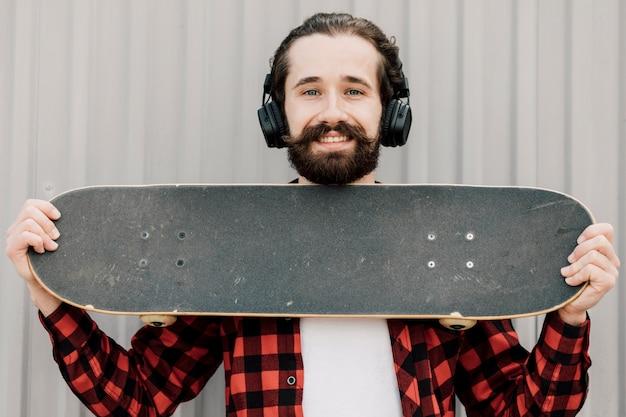 Vorderansicht des mannes skateboard halten Kostenlose Fotos