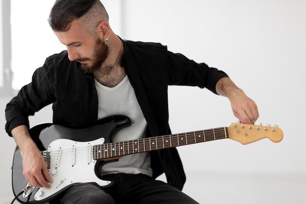 Vorderansicht des musikers, der e-gitarre spielt Kostenlose Fotos